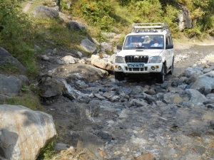 Here's the jeep negotiating the washout after considerable road repair work by by-standers.