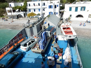Here's the big ferry picking us up at  Loutro. A day later than we'd expected.mloutro has a population of about 90 people. The ferry made three stops to off load various supplies. Here a truck with doors and windows is being off loaded onto the beach. See the people there relaxing on their beach chairs?