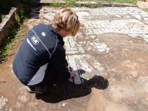 Kathy examining the ancient mosaics at one of the temple ruins.