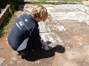 Kathy examining the ancient mosaics at one of the temple ruins.